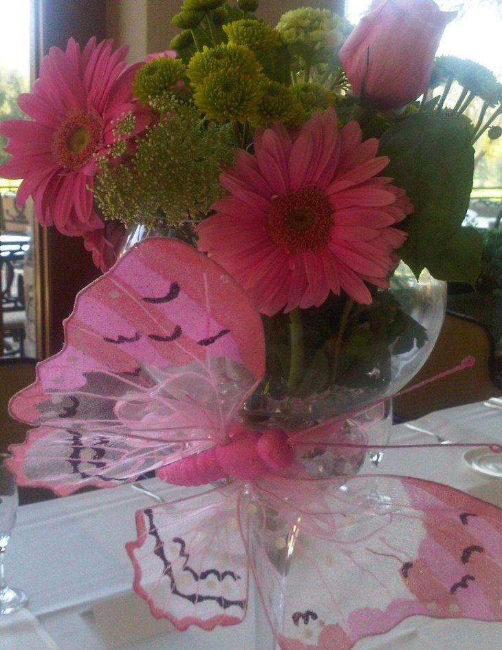 Pink butterfly and floral centerpiece decoration on girl baby shower table