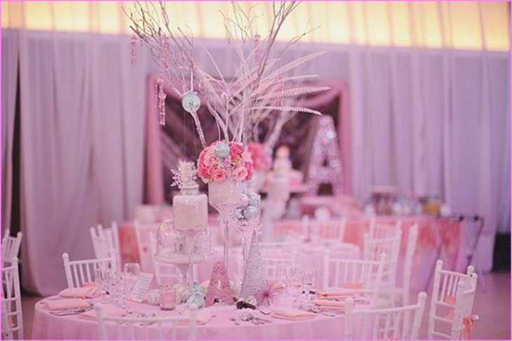 Pink flowers and twigs decor on winter wonderland table