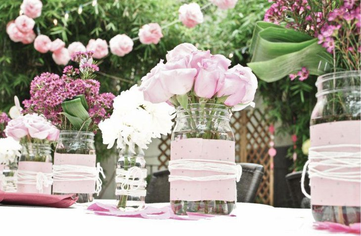 Pink themed flower arangement in mason jars for wedding table