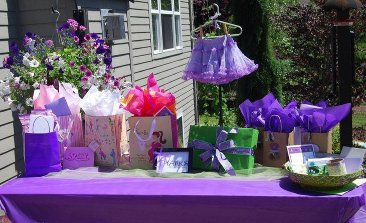 Purple baby girls shower decorations on table