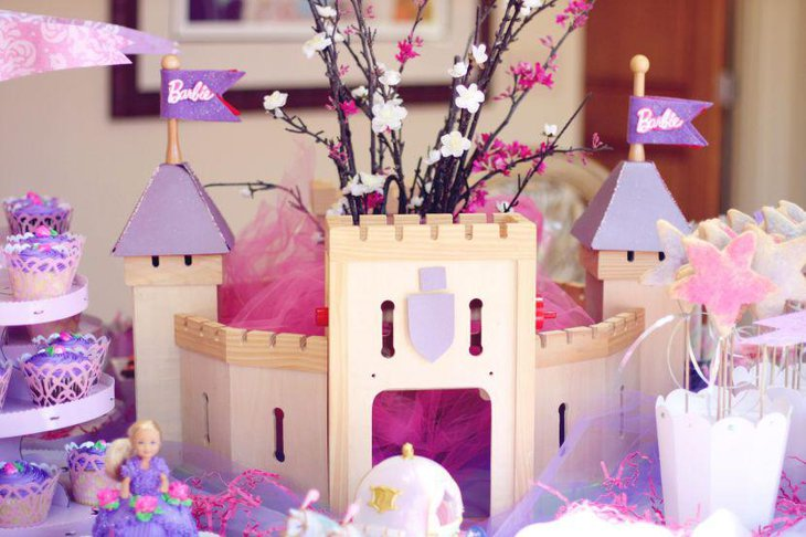 Purple Barbie themed castle decor on birthday party table