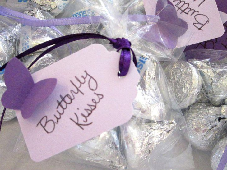 Purple butterfly decorations on baby shower sweets table