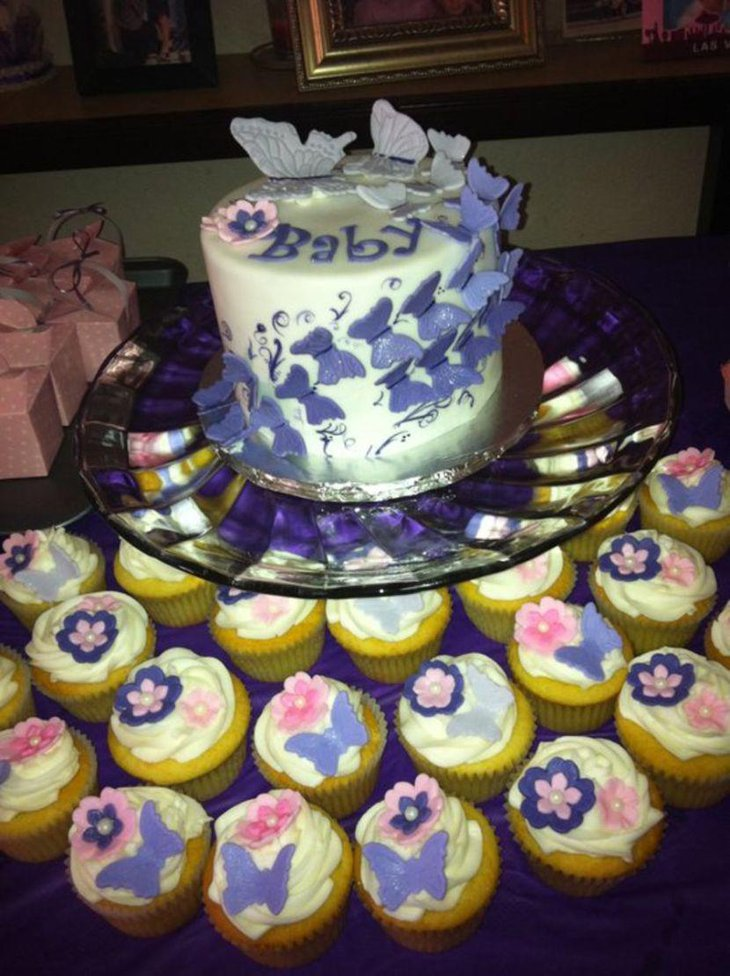 Purple butterfly themed cake and cupcake decorations on baby shower table