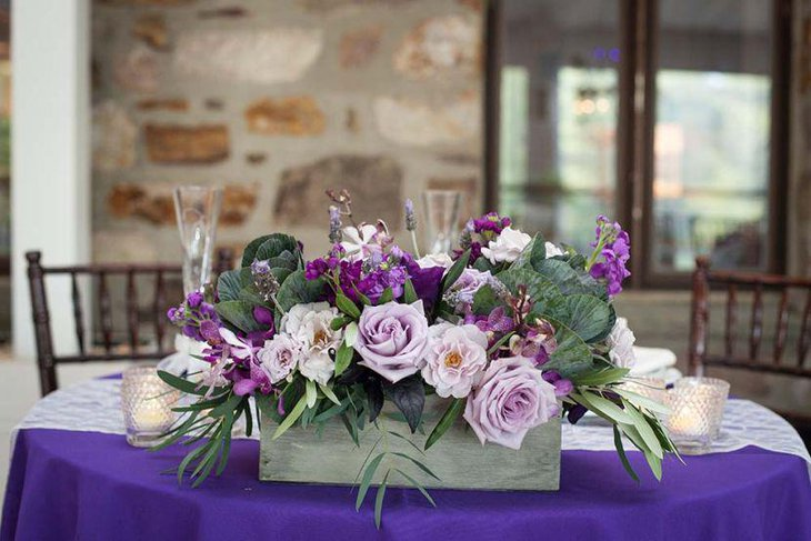 Purple floral arrangement on wedding party table