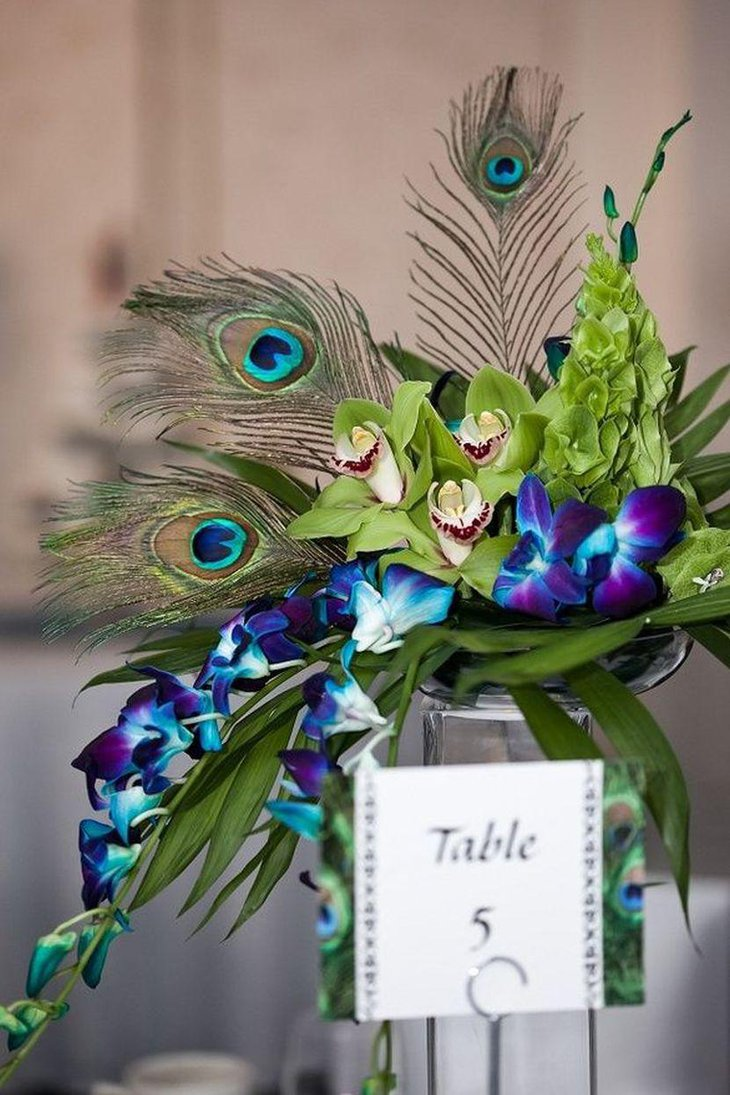 Purple wedding table decor with peacock feathers and orchid decorations