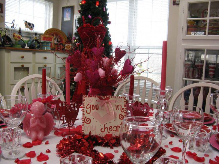 Red angel figurine and candles on Christmas table