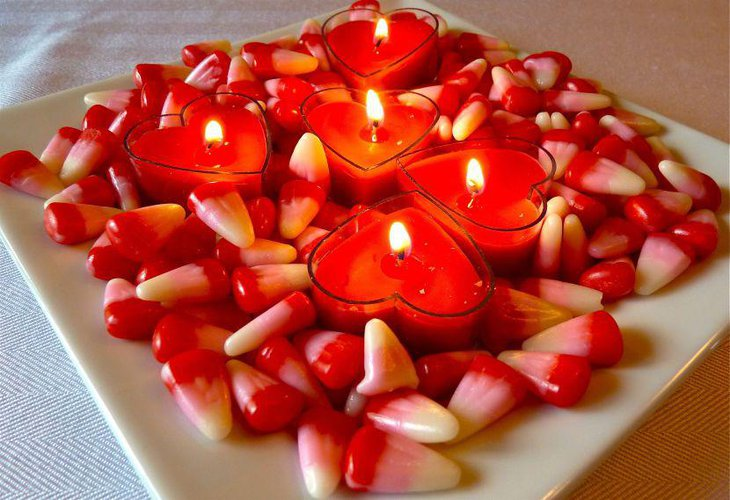Red heart candles with candy cane decor on Valentines table