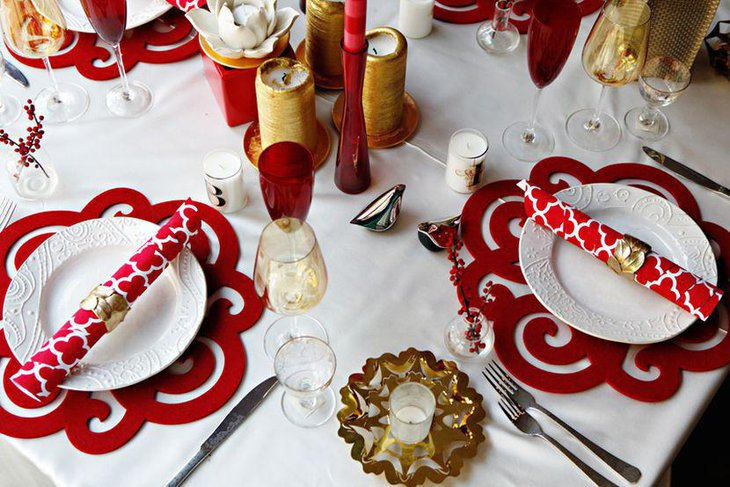 Red mats offer a contrasting effect with white candles and dinner plates