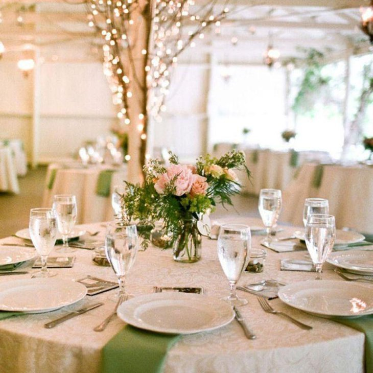 Romantic country wedding reception table decked with floral centerpiece