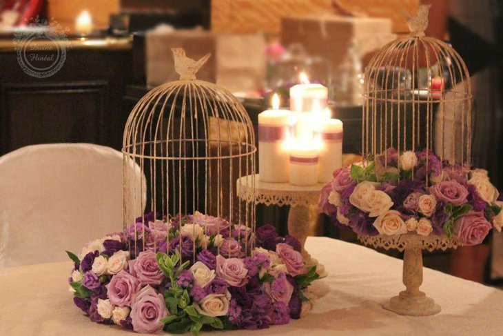 Romantic wedding tablescape with birdcage on purple floral wreath
