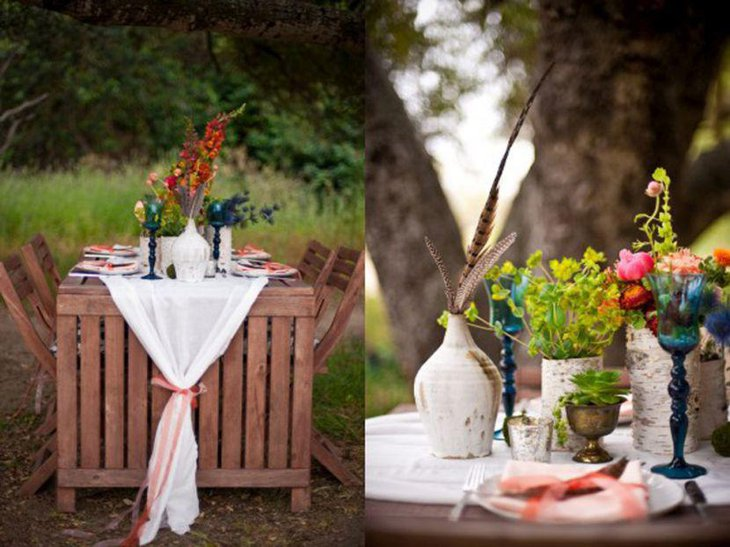 Rustic colourful outdoor party table setting with candlestands and flower vases