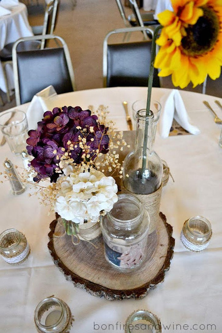 Rustic purple wedding table decor with flowers wooden slab and jars