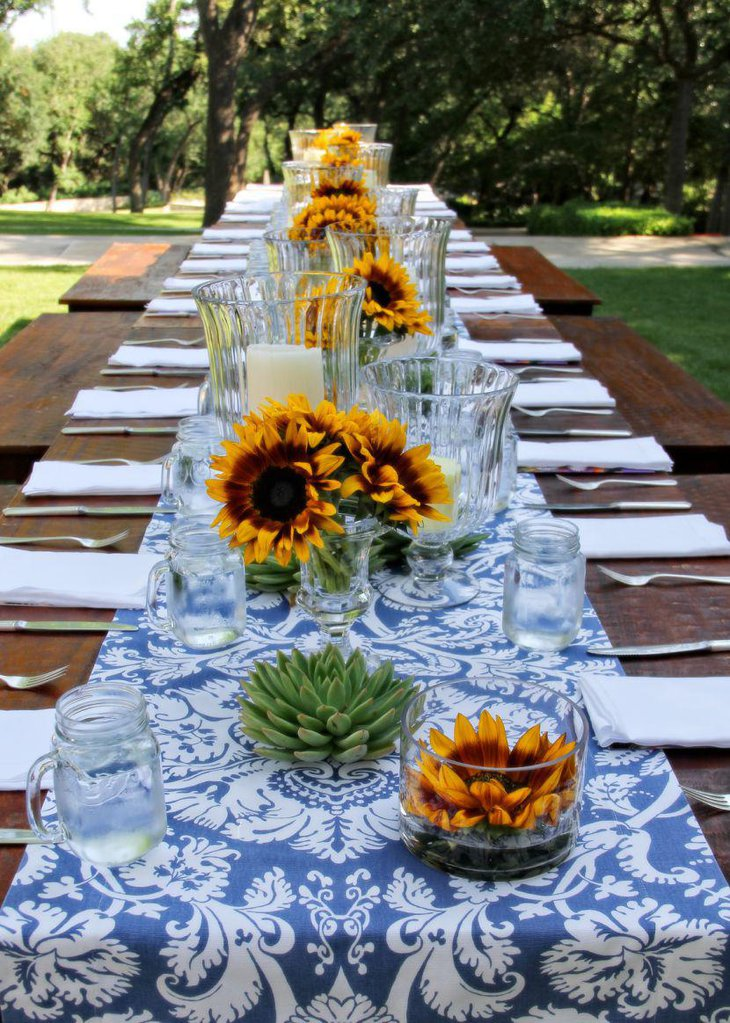 Rustic table decorated with blue printed runner and yellow sunflowers