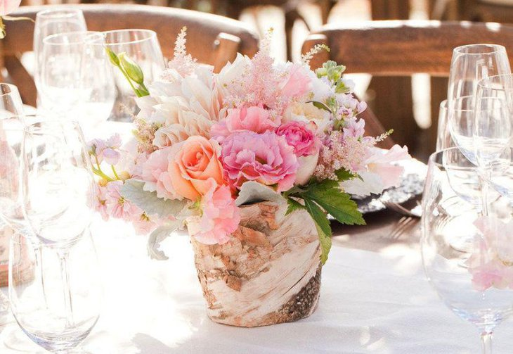 Rustic vase with flowers centerpiece on spring wedding table