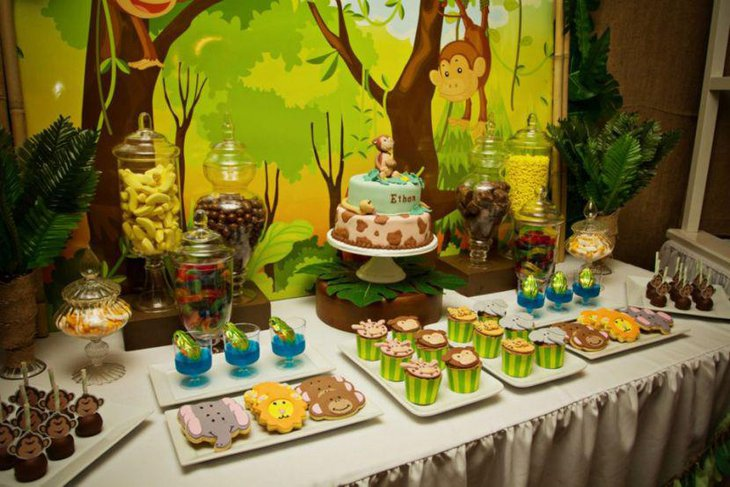 Safari theme dessert table with lots of greens and animal shaped yummy desserts
