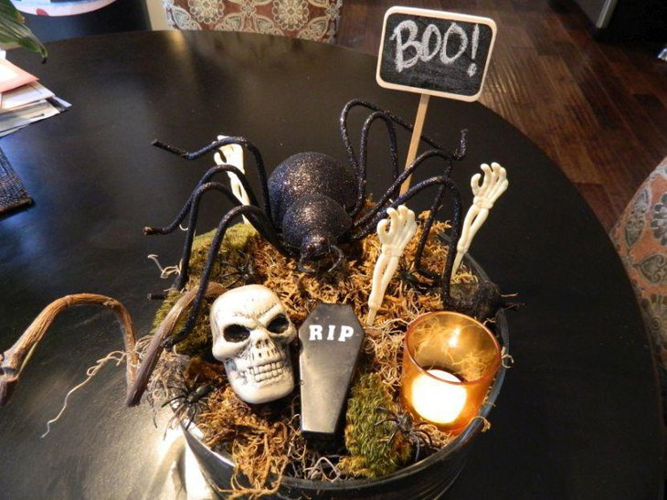 Scary DIY Halloween table centerpiece with a black bucket filled with dry grass skull spider and sipper with candle