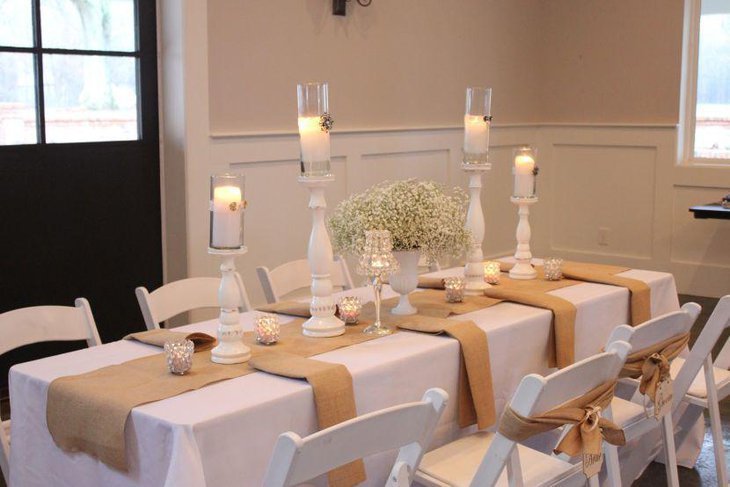 Scented White Candles On Wooden Stands As Dining Table Centerpieces