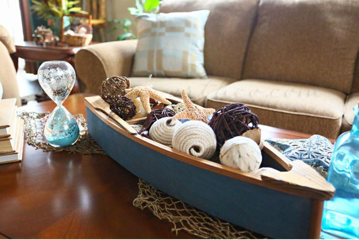 Sea themed coffee table decor with a boat and hourglass