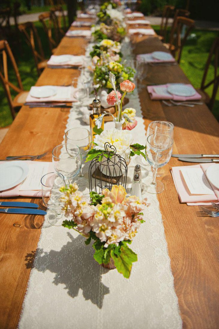 Simple floral country wedding table decked with rustic birdcage