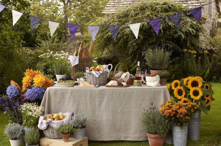 Simple garden party table setting with food in wicker baskets