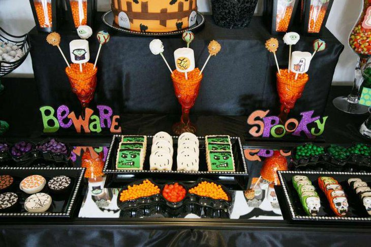 Spooky Halloween party table for kids with ghost shaped candies and treats