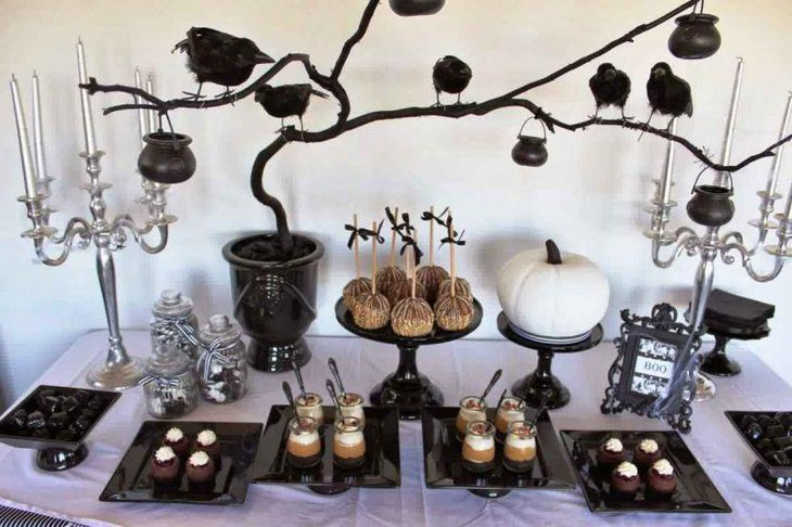Spooky Halloween table decor with white pumpkin and black tree branch with ravens