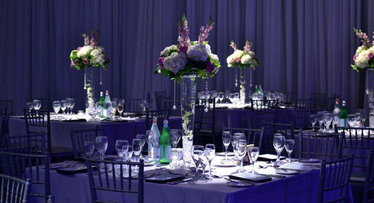 Square Wedding Table Ideas with Purple Satin Linen and tall Centerpiece Glass Vase