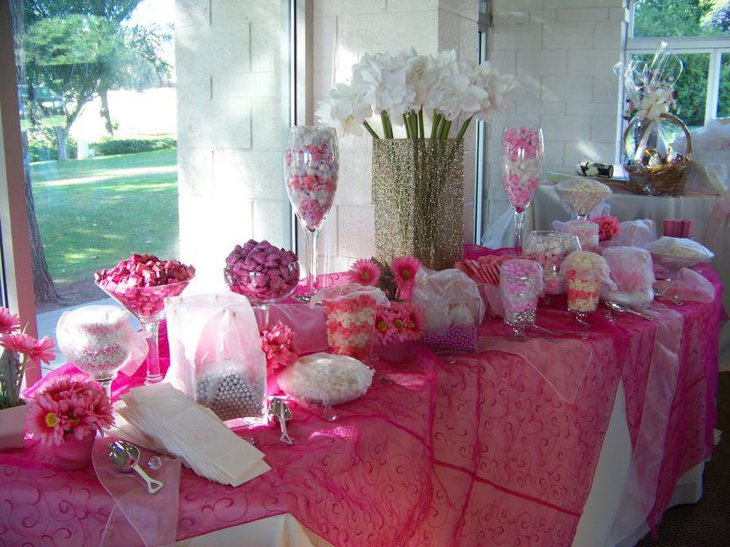 Stunning baby shower candy tablescape with pink candies ans flowers