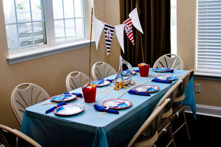 Stunning nautical themed baby shower table decor with net and sail boat centerpiece