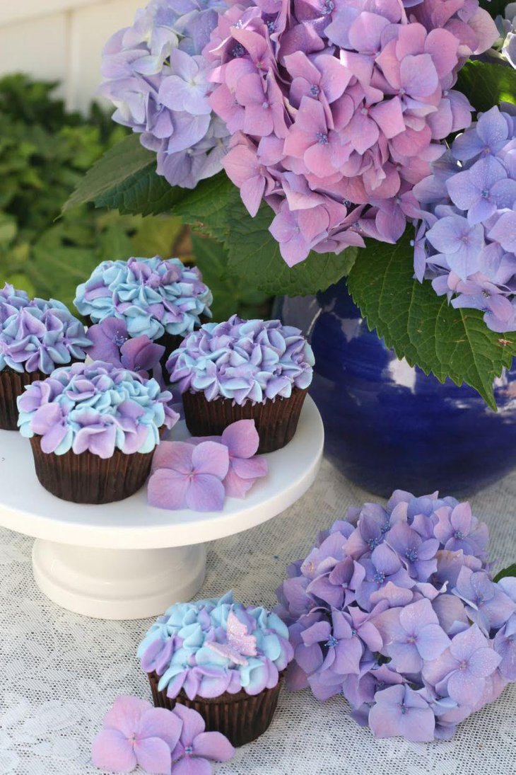 Stunning party table decor with purple hydrangea cupcakes and flowers