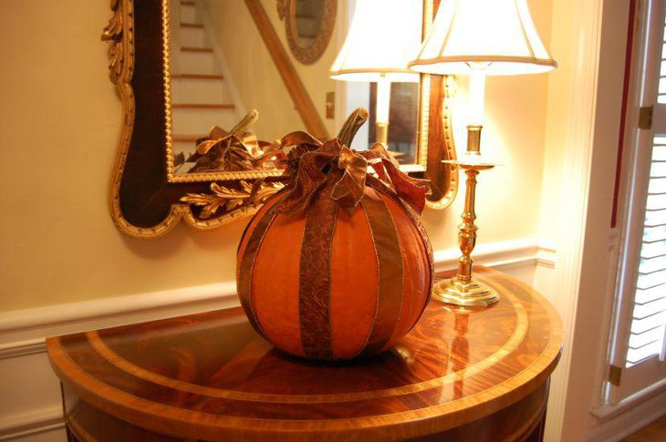 Stunning pumpkin dressed in golden ribbon for Halloween table