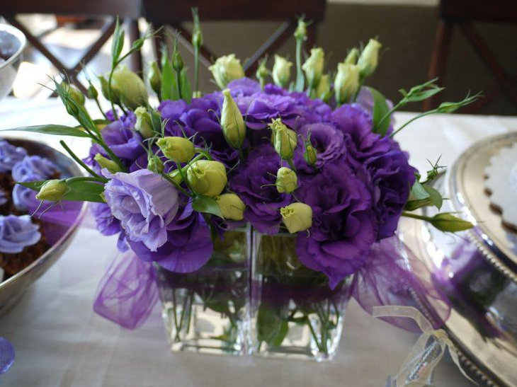 Stunning purple accented floral vase decoration on party table