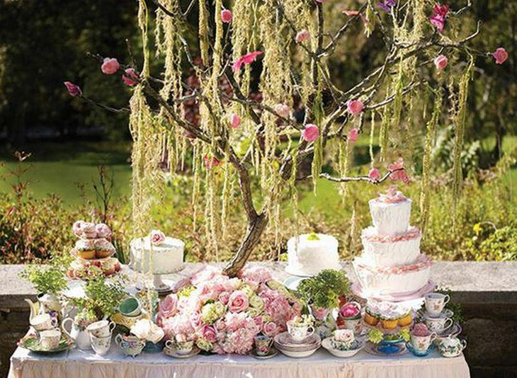 Stunning spring garden party table decor with floral arrangement and branch centerpiece