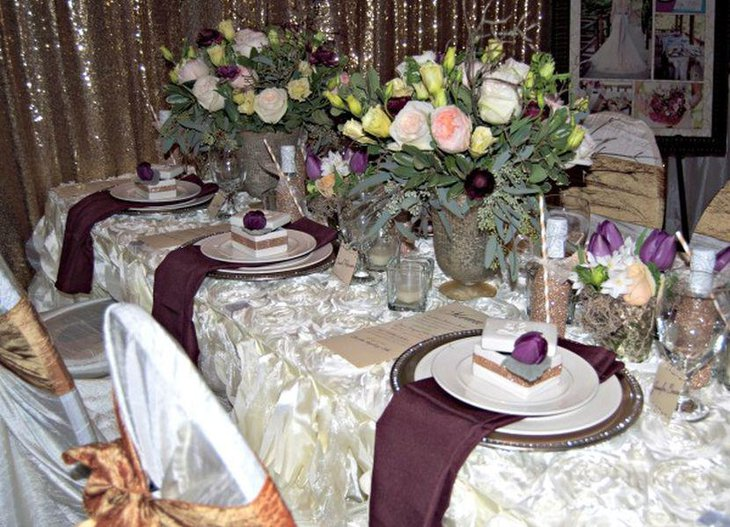 Stunning wedding table decor with purple napkins and flower buds