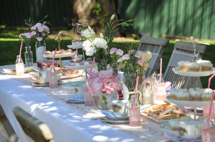 Subtle white and pink themed summer garden party table decoration with flowers and leaves in glass jars