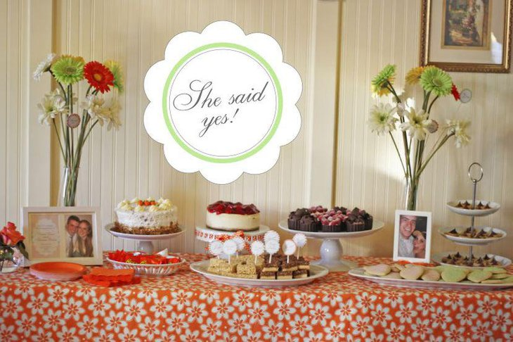 Sweet engagement party dessert table decor with fresh floral arrangements and assorted sweets