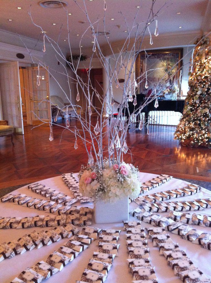 This winter wonderland table looks gorgeous with a twig centerpiece decked up with hanging crystals