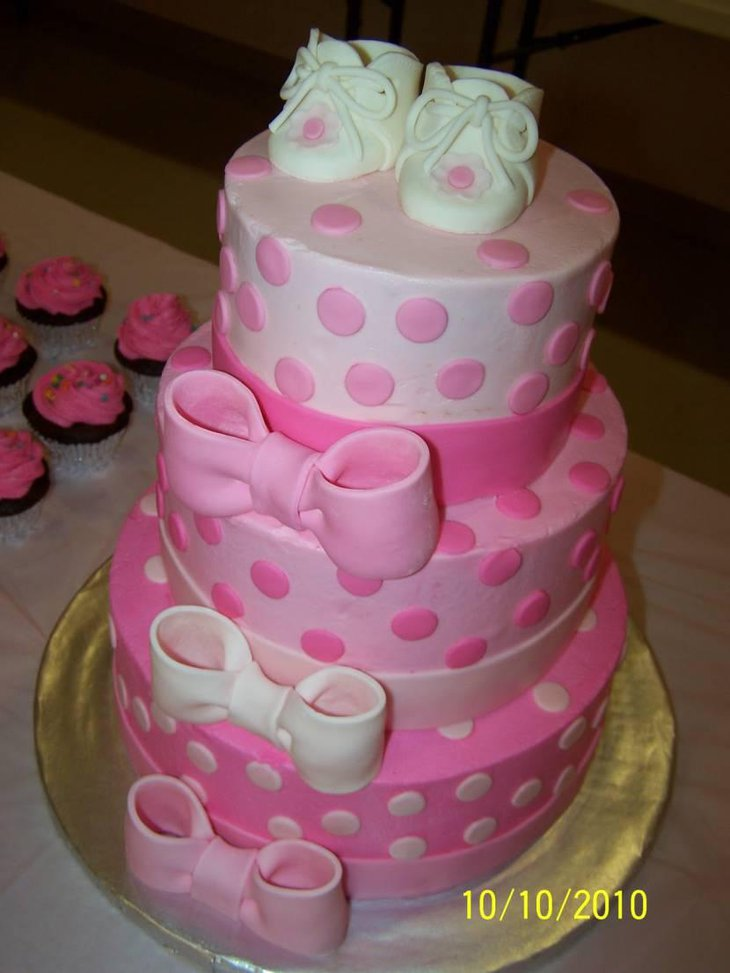 Three tier baby shower cake with cute baby shoes on top