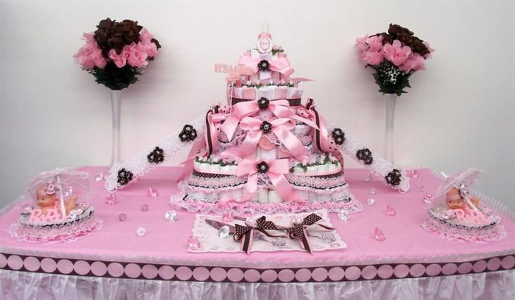Tiered baby shower cake for a girl with pink ribbons
