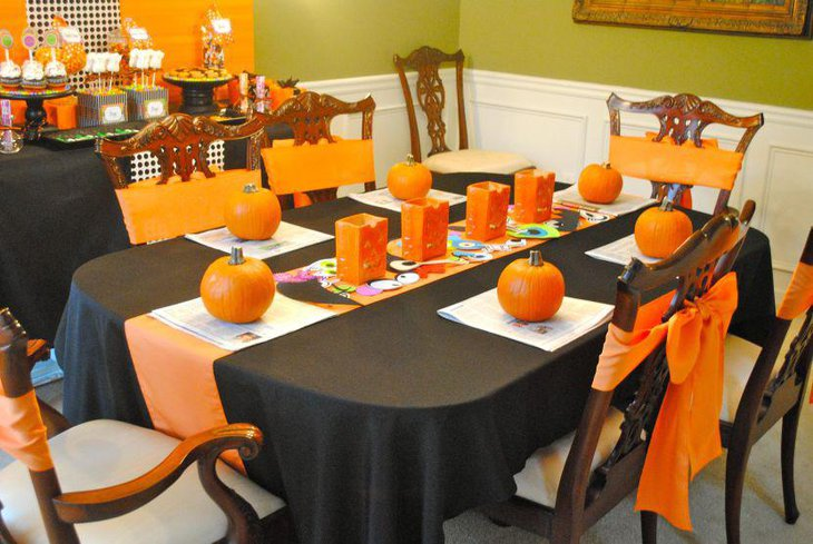 Unique orange and black themed Halloween table with pumpkin decorations