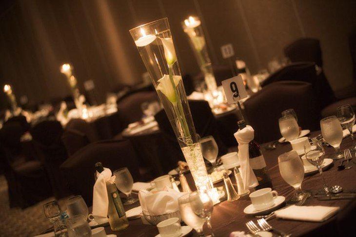 Unique wedding reception idea with floating candles and lilies in tall glass centerpiece