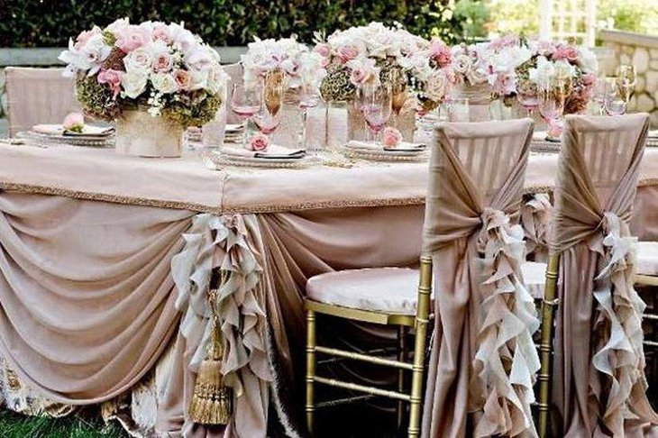 Unique wedding table decor with floral bunches in pretty pink and frilly drapes