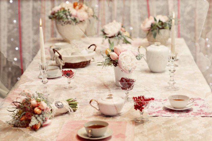 Vintage tea party table settign with decorative tea pots dry flowers and crystal candle holders with candles