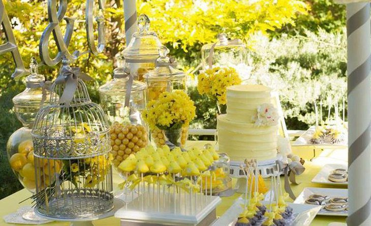 Wedding dessert table decor with bright yellow flowers
