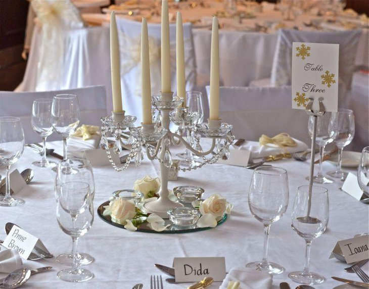 Wedding reception table decorations with white candles on crystal candle holder