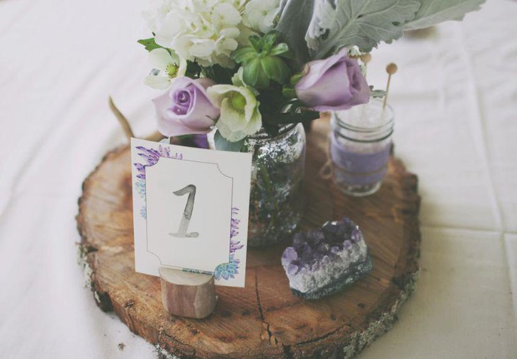 Wedding table decor with custom wedding table number and flowers with hints of purple