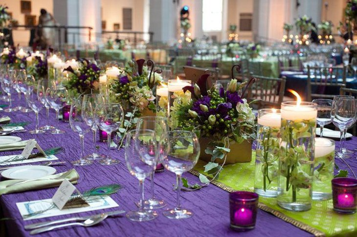 Wedding table decor with low floral centerpieces in purple tones