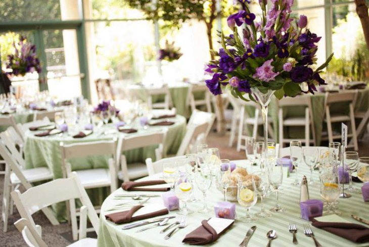 Wedding table decor with purple and green floral centerpiece
