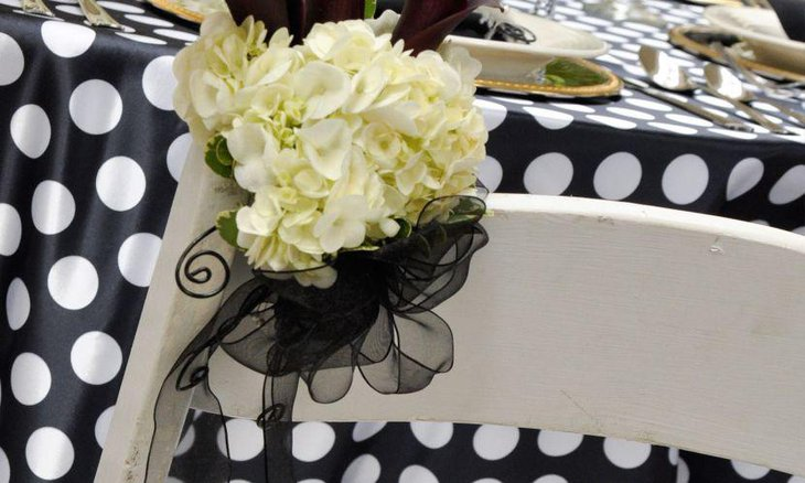 Wedding table setting with white lilies white and black polka dotted tablecloth with gold embossed plates & 35 Black And White Wedding Table Settings | Table Decorating Ideas