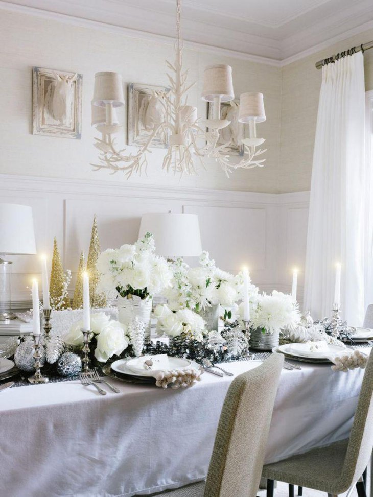 White Christmas tablescape with flowers and lit up candles